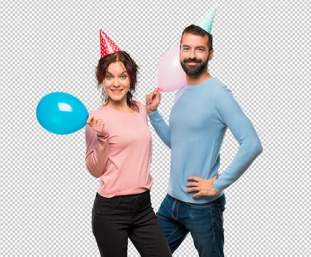 Paare mit den ballonen und geburtstagshüten, die mit den armen an der hüfte und am lächeln aufwerfen