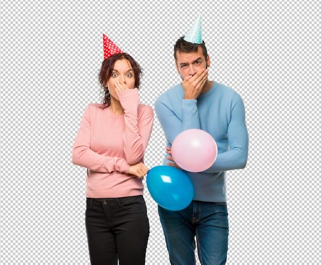 Paare mit den ballonen und geburtstagshüten, die mund für das sagen etwas unpassendes umfassen