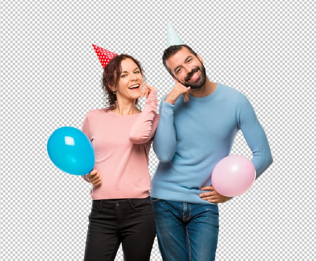 Paare mit den ballonen und geburtstagshüten, die telefongeste machen. ruf mich zurück zeichen