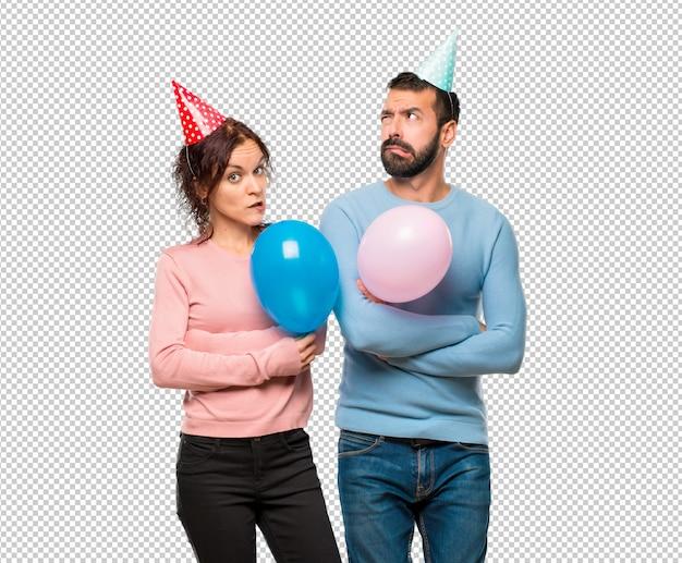 Paare mit den ballonen und geburtstagshüten, die zweifel haben und mit gesichtsausdruck verwechseln