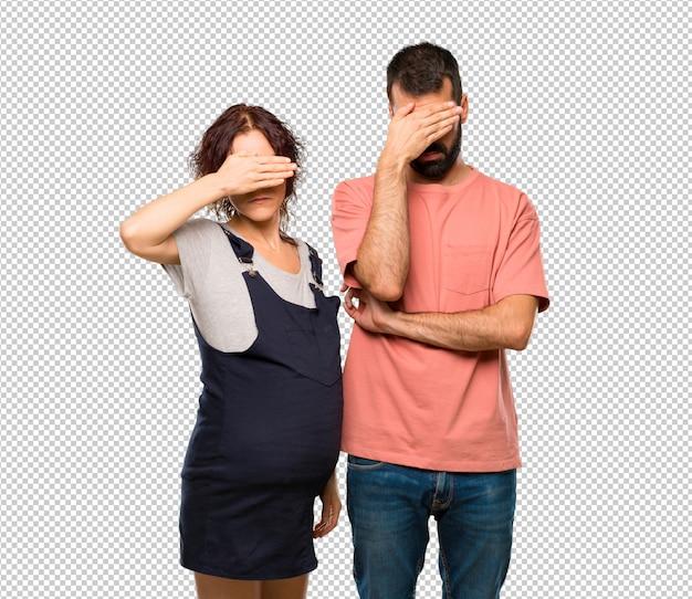 Paare mit den bedeckungsaugen der schwangeren frau durch hände. ich will nichts sehen