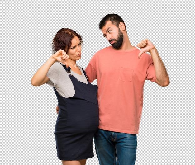Paare mit der schwangeren frau, die daumen zeichen mit negativem ausdruck unten zeigt