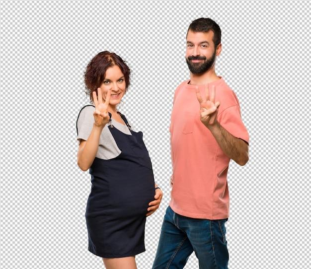 Paare mit der schwangeren frau, die drei mit den fingern glücklich ist und zählt