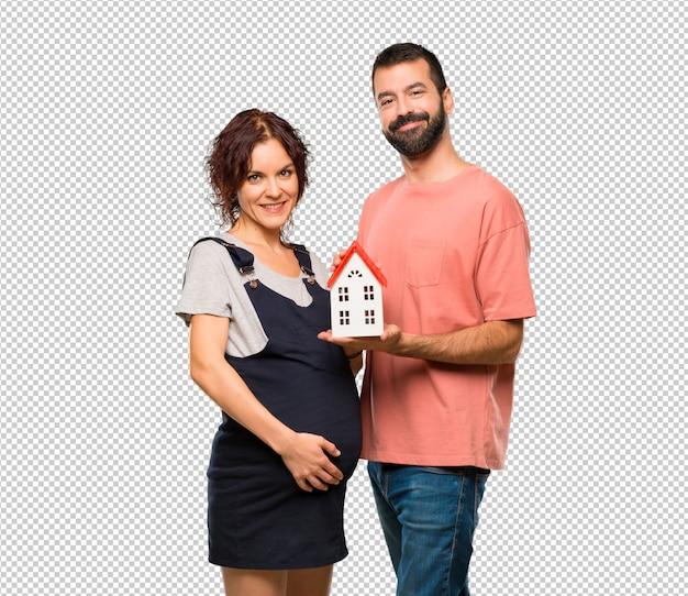 Paare mit der schwangeren frau, die ein kleines haus hält