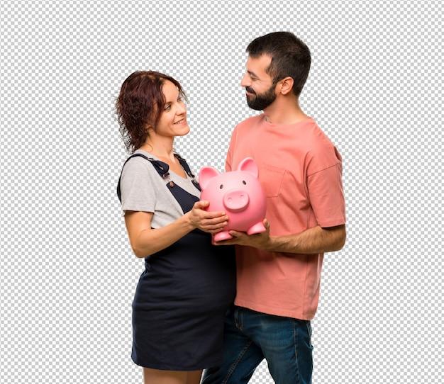 Paare mit der schwangeren frau, die ein piggybank hält