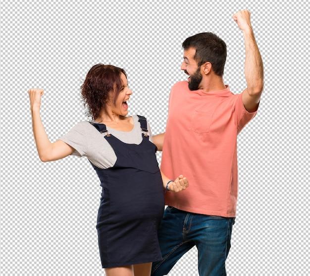 Paare mit der schwangeren frau, die einen sieg in siegerposition feiert