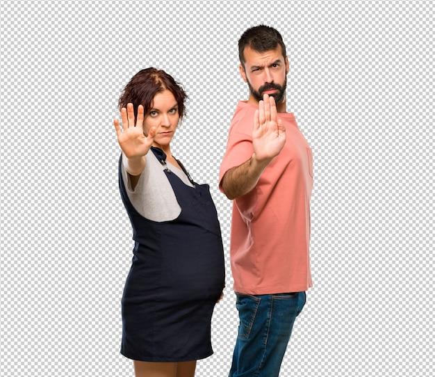Paare mit der schwangeren frau, die endgeste mit ihrer hand macht, die eine situation leugnet, die falsch denkt