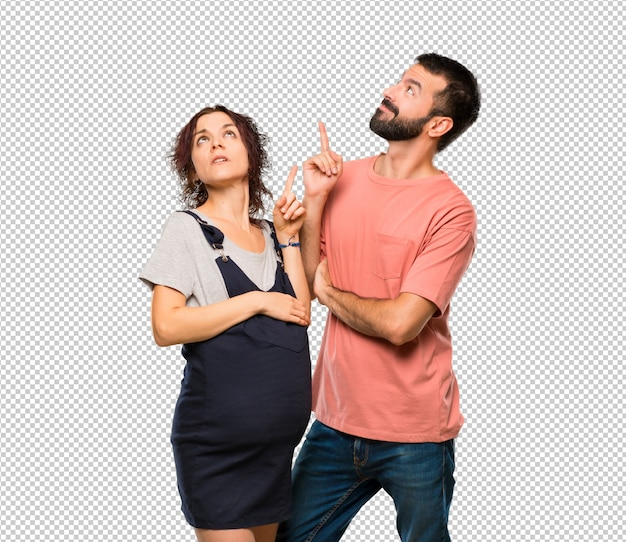 Paare mit der schwangeren frau, die mit dem finger eine großartige idee zeigt und oben schaut
