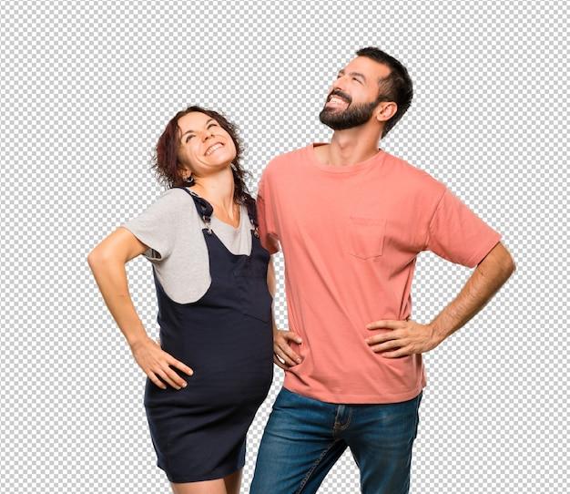 Paare mit der schwangeren frau, die mit den armen an der hüfte und am lachen aufwirft