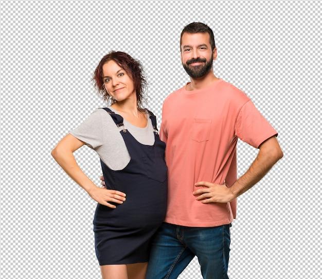 Paare mit der schwangeren frau, die mit den armen an der hüfte und am lächeln aufwirft
