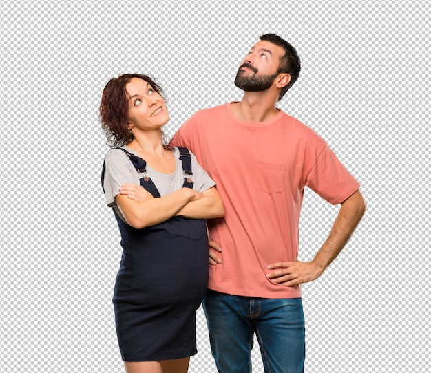 Paare mit der schwangeren frau, die oben beim lächeln schaut