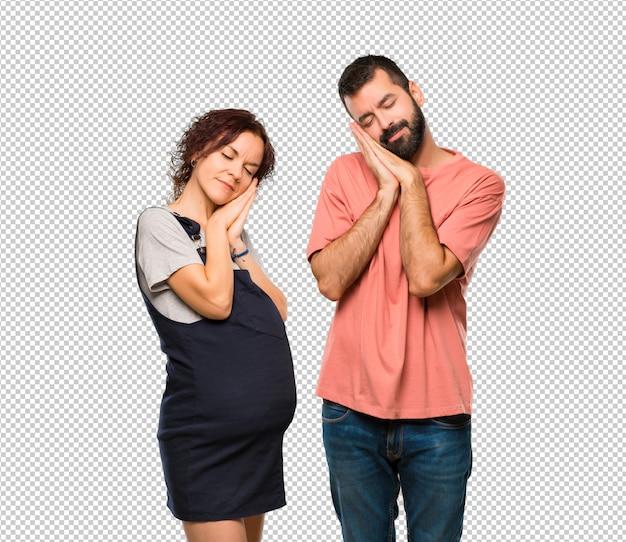 Paare mit der schwangeren frau, die schlafgeste macht. entzückender süßer ausdruck