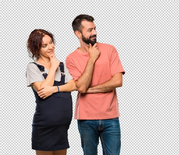 Paare mit der schwangeren frau, die zur seite mit der hand auf dem kinn schaut
