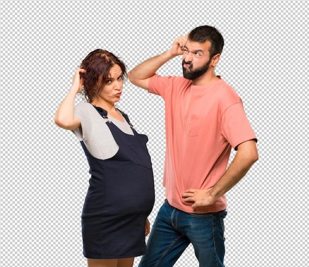 Paare mit der schwangeren frau, die zweifel hat und mit verwirren gesicht beim verkratzen des kopfes