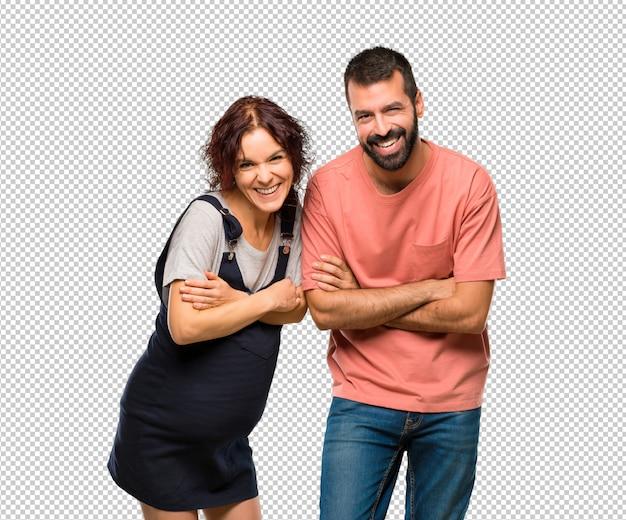 Paare mit der schwangeren frau, welche die arme beim lächeln gekreuzt hält