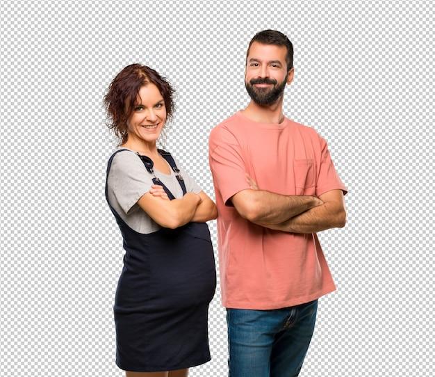 Paare mit der schwangeren frau, welche die arme hält, kreuzten in seitlicher position beim lächeln