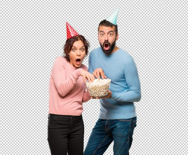 Paare mit geburtstagshüten und popcorn essend
