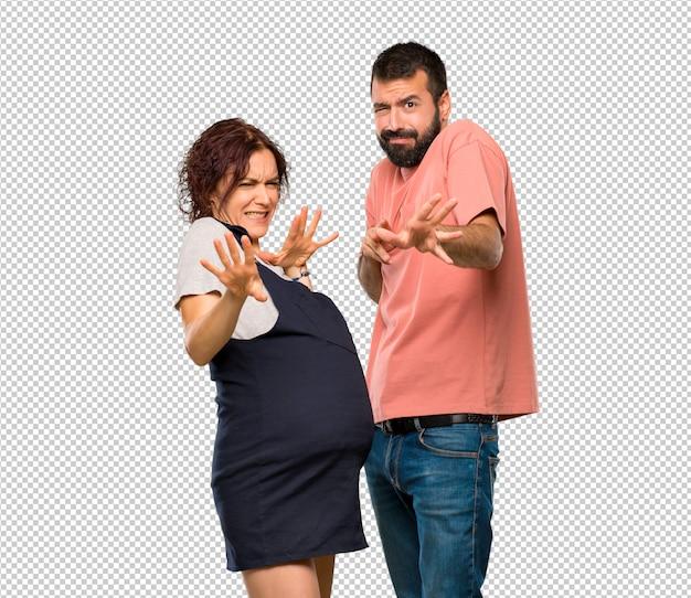 Paare mit schwangeren frauen sind ein kleines bisschen nervös und erschrocken, hände an der front ausdehnend
