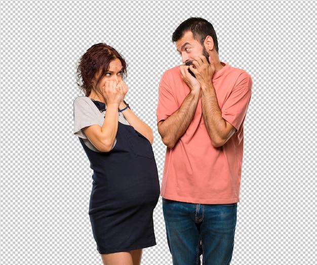 Paare mit schwangeren frauen sind ein kleines bisschen nervös und erschrocken, hände zum mund setzend