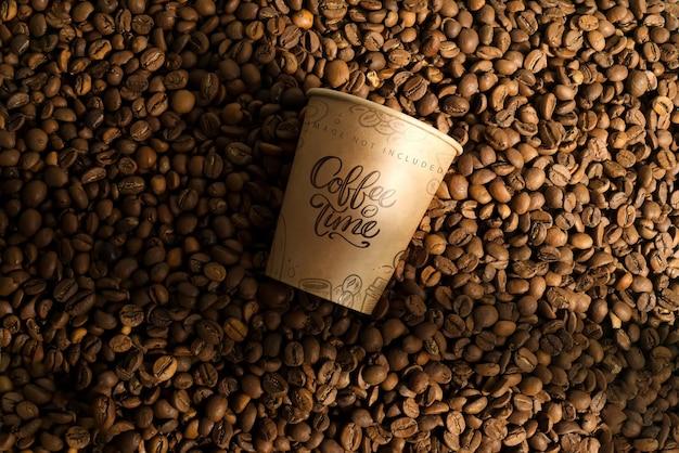 Pappbecher modell auf einem kaffeebohnen. kaffee-konzept zum mitnehmen