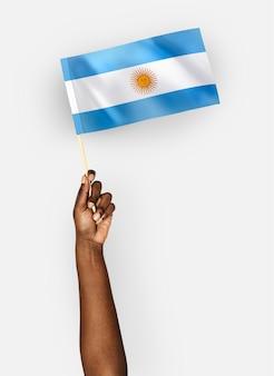 Person, die die flagge der argentinien-republik wellenartig bewegt