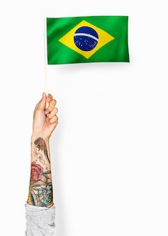 Person, die die flagge der föderativen republik brasilien wellenartig bewegt