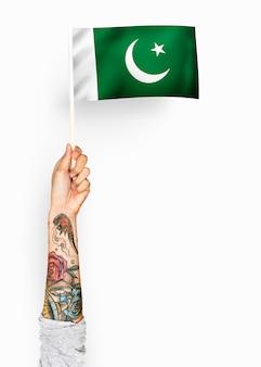 Person, die die flagge der islamischen republik von pakistan wellenartig bewegt