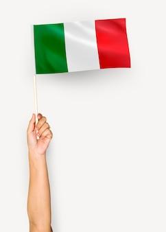 Person, die die flagge der italienischen republik wellenartig bewegt