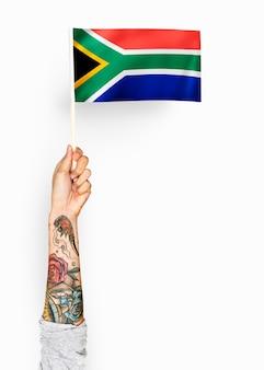 Person, die die flagge der republik von südafrika wellenartig bewegt