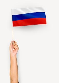 Person, die die flagge der russischen föderation wellenartig bewegt