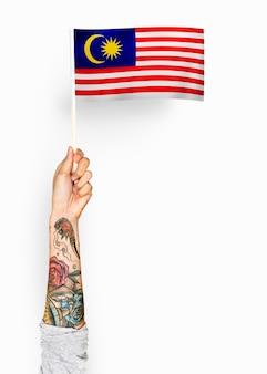 Person, die die flagge von malaysia wellenartig bewegt