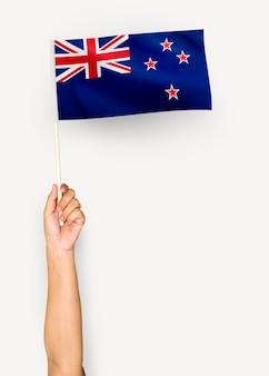 Person, die die flagge von neuseeland wellenartig bewegt