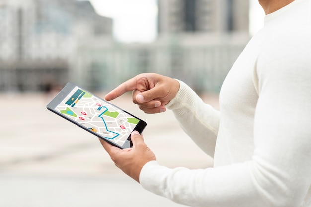 Person, die draußen auf karte von einer tablette schaut
