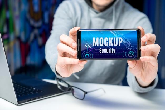 Person, die ein digitales sicherheitsmodell des smartphones hält