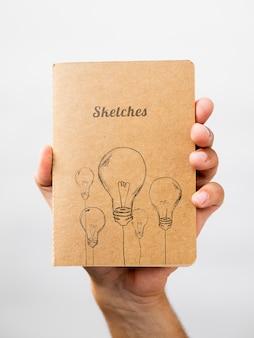 Person, die ein skizzenbuch hält