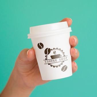 Person, die eine kaffeepapiertasse auf blauem hintergrund hält