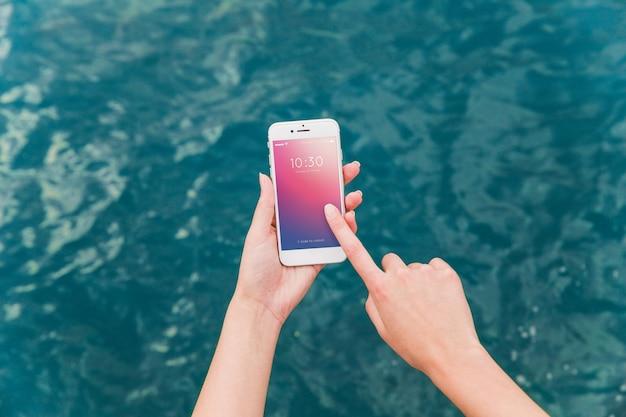 Person, die smartphonemodell auf seehintergrund verwendet