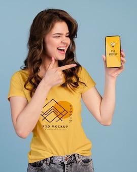 Person mit aufgeregtem ausdruck, die auf das telefonmodell zeigt