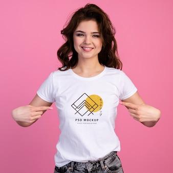 Person mit aufgeregtem ausdruck, die auf t-shirt-modell zeigt