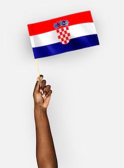 Person weht die flagge der republik kroatien