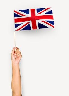 Person weht die flagge des vereinigten königreichs von großbritannien und nordirland