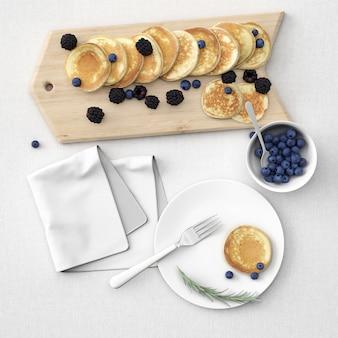 Pfannkuchen an bord und teller mit beeren