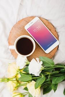Pfingstrosenblumenmodell mit kaffee und smartphone