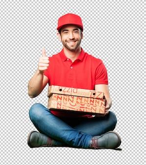 Pizzahändler, der einen pizzakasten halten sitzt