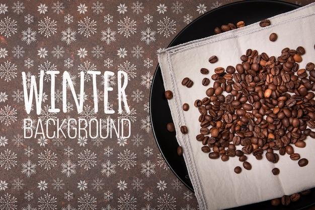 Platte mit kaffeebohnen und winterhintergrund