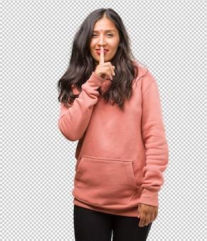 Porträt der jungen indischen frau der eignung, die ein geheimnis hält oder um ruhe, ernstes gesicht, gehorsamkonzept bittet