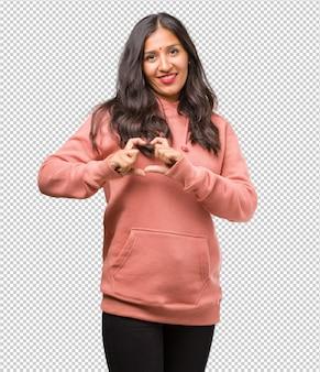 Porträt der jungen indischen frau der eignung, die ein herz mit den händen macht, das konzept der liebe und der freundschaft ausdrückt, glücklich und das lächeln