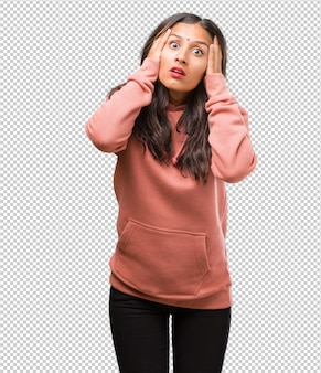 Porträt der jungen indischen frau der eignung frustriert und hoffnungslos, verärgert und traurig mit den händen auf kopf