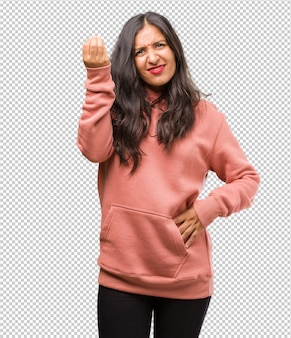 Porträt der jungen indischen frau der fitness, die eine typische italienische geste tut, lächelt und geradeaus schaut, symbol oder ausdruck mit hand, sehr natürlich