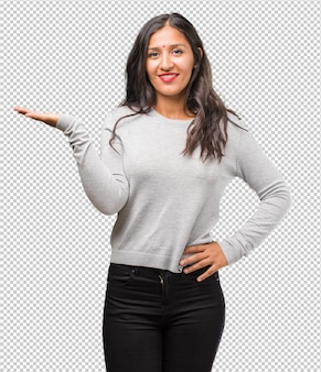 Porträt der jungen indischen frau, die etwas mit händen hält, ein produkt zeigt, lächelnd und fröhlich, ein imaginäres objekt anbietend